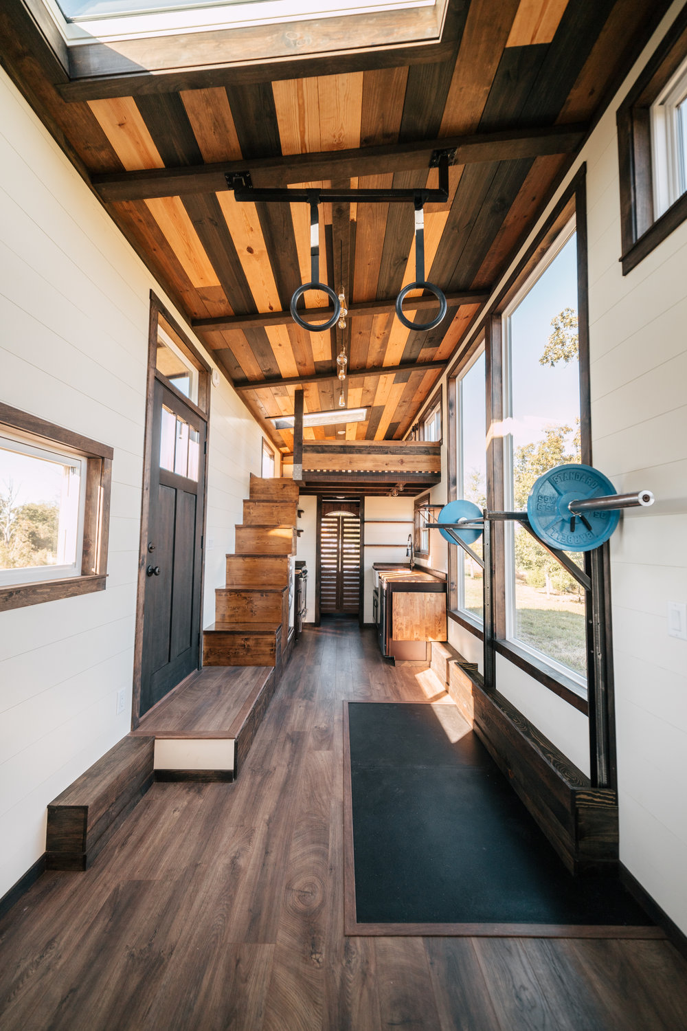 The Silhouette by Wind River Tiny Homes - integrated exercise floor, custom Olympic squat/bench rack, fold down table, storage stairs, gym rings, LED edison bulb light fixture, multi stained ceiling
