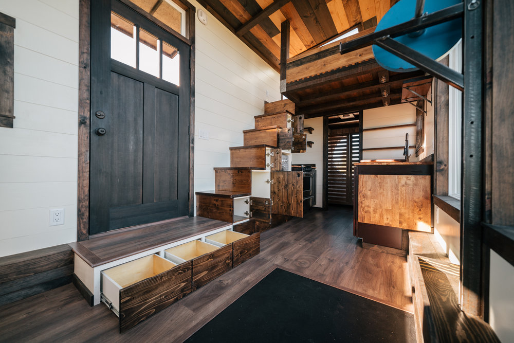 The Silhouette by Wind River Tiny Homes - custom Olympic squat/bench rack, washer dryer combo, storage stairs, shaker style cabinets, multi stained ceiling, fold down table