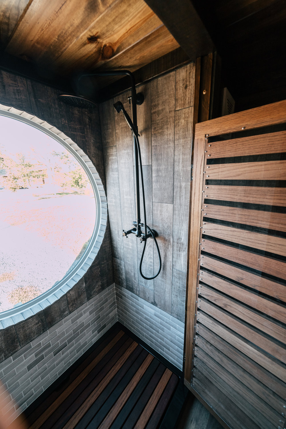 The Silhouette by Wind River Tiny Homes - oak wood slat/Plexiglass shower stall doors, limestone tile, faux wood tile, oil rubbed bronze rain shower head with handheld, cumaru wood shower deck insert
