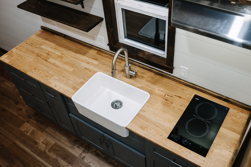 The Noah by Wind River Tiny Homes - farmhouse sink, butcher block counter, gray shaker cabinets, open shelving, shiplap, electric glass cooktop