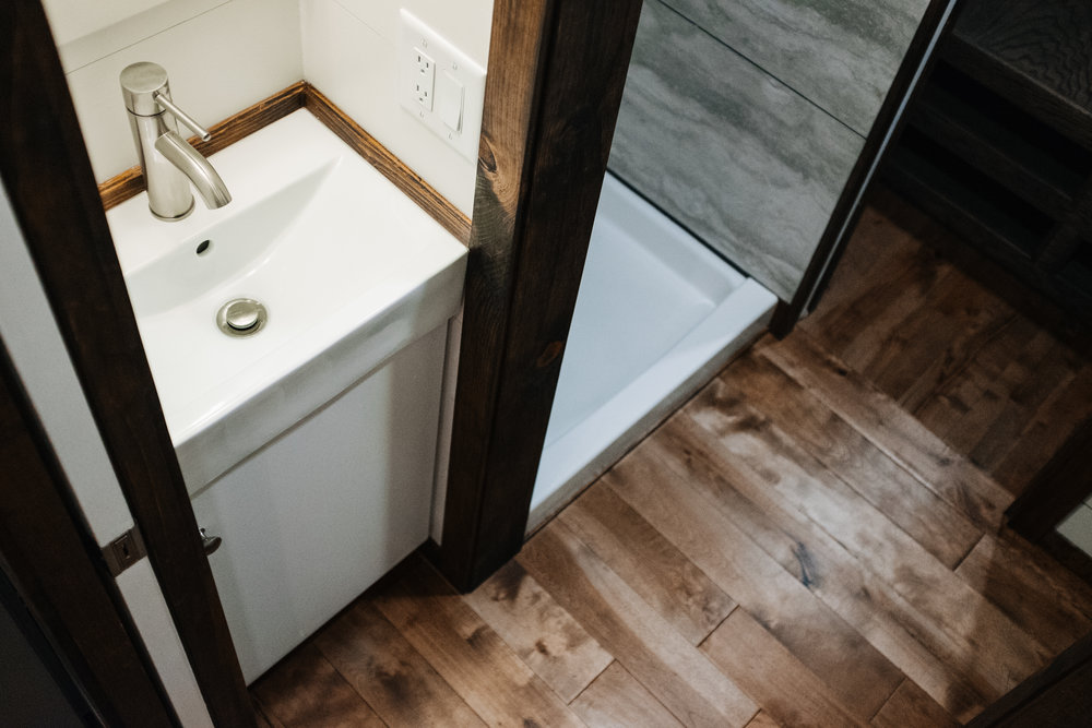 The Noah by Wind River Tiny Homes - birch hardwood flooring, compact bathroom vanity, tile shower stall
