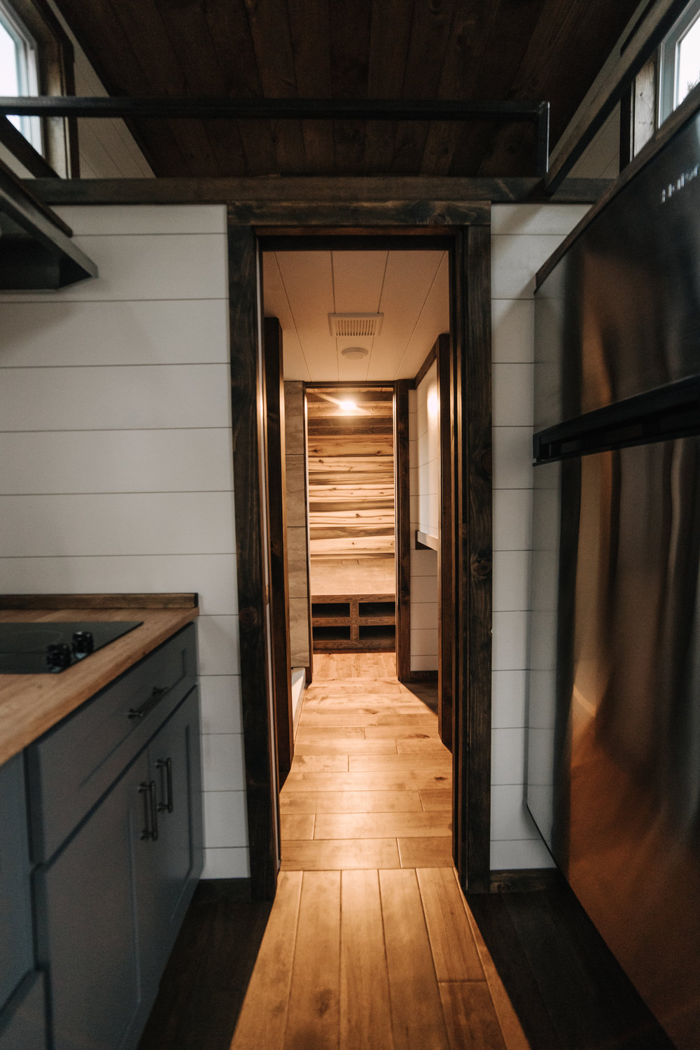 The Noah by Wind River Tiny Homes - 3/4 size stainless fridge, custom welded steel ladder & railing, gray shaker cabinets, butcher block counter