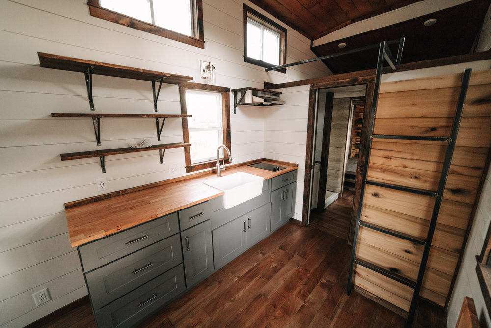 The Noah by Wind River Tiny Homes - natural poplar accent wall, gray shaker cabinets, custom welded steel ladder & railing, butcher block counter, farmhouse sink, open shelving