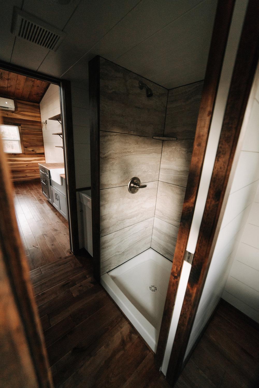 The Noah by Wind River Tiny Homes - birch hardwood flooring, compact bathroom vanity, tile shower, pocket door, brushed nickel shower trim