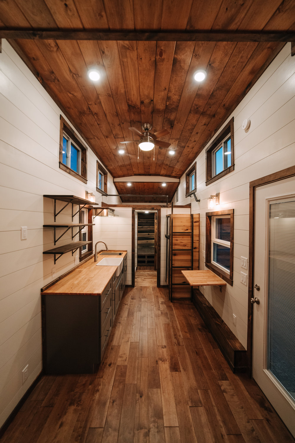 The Noah by Wind River Tiny Homes - farmhouse sink, butcher block counters, gray shaker cabinets, birch hardwood floors, custom welded steel ladder