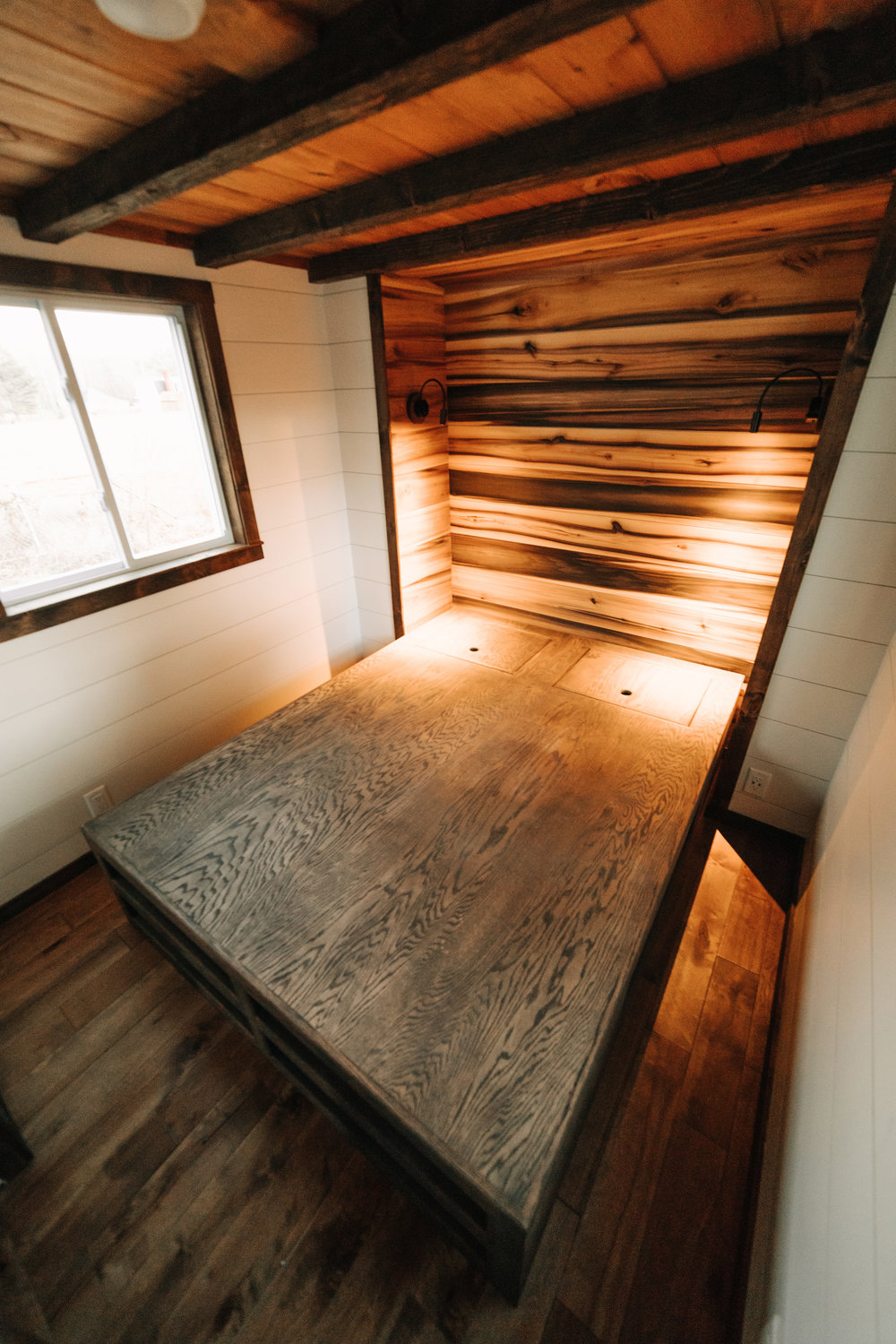 The Noah by Wind River Tiny Homes - natural poplar accent wall, shiplap, custom built storage bed platform