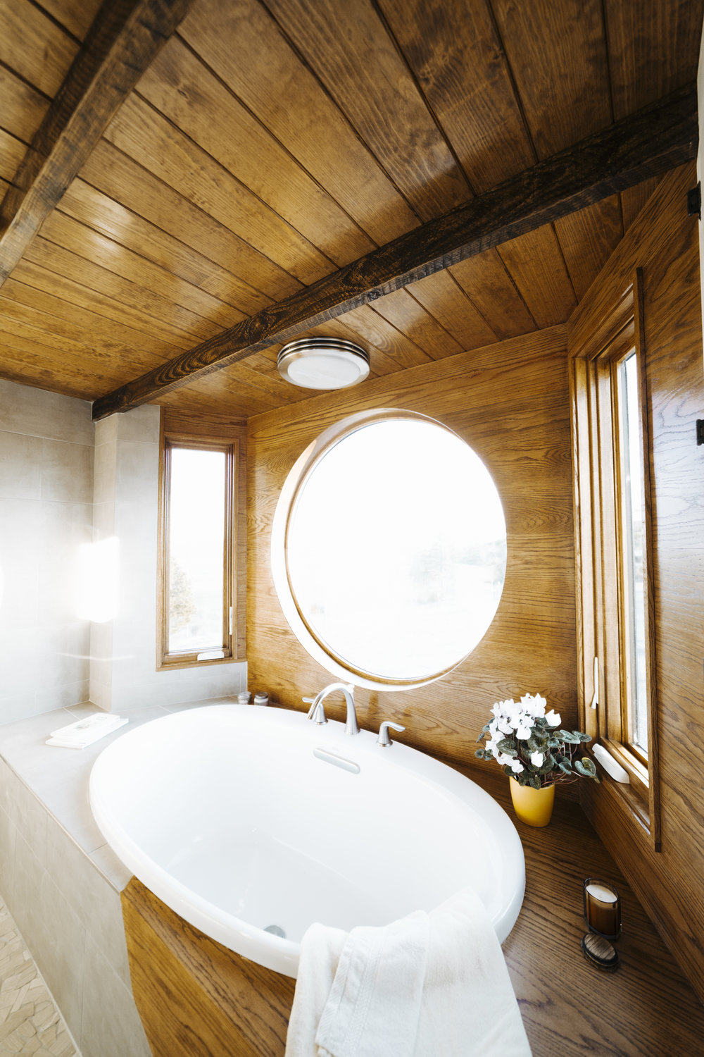 The Monocle Tiny House by Wind River Tiny Homes. Featuring a round window in the custom bathroom.