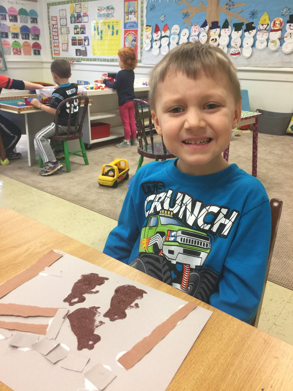 Corbin, Perkins, a four year old student, works on his hibernation art.