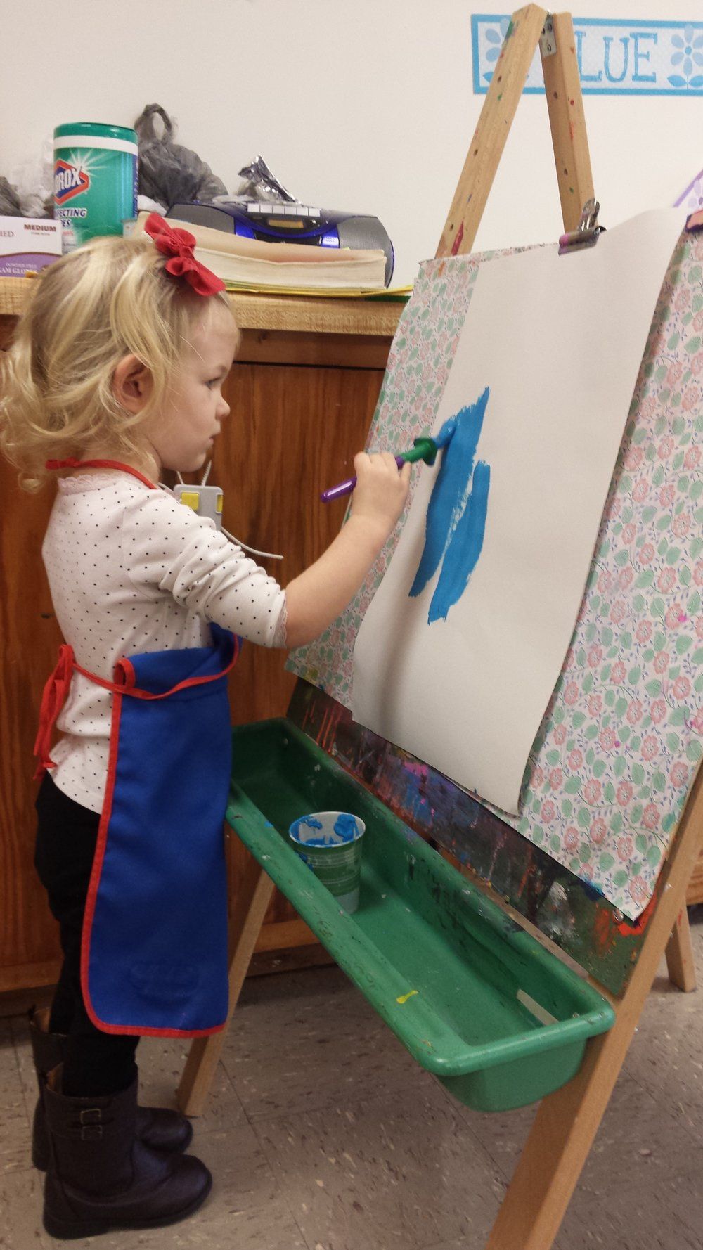 Acacia Wiggins, a one year old student, is working on her winter art in class.