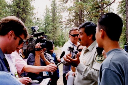 Juan Palma addressing media in lake tahoe, ca during the 1997 president clinton visit. His son JOnathan looks on.