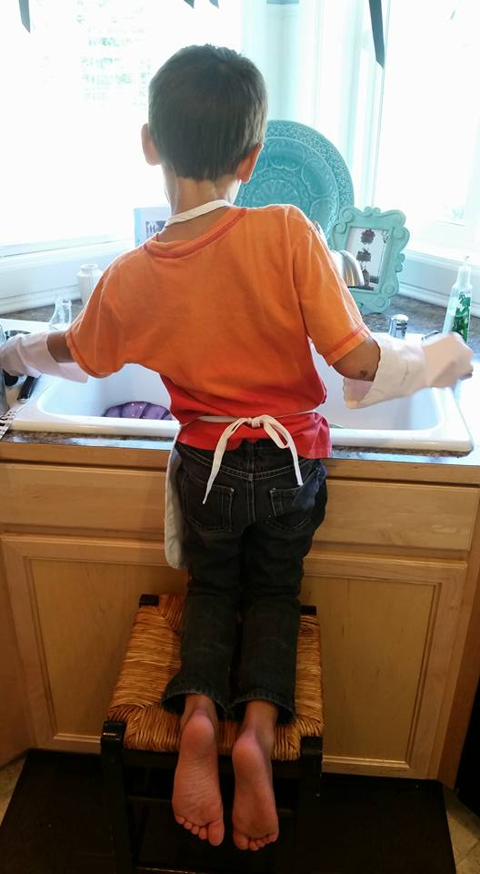 Our grandson Leo about a year ago doing dishes.