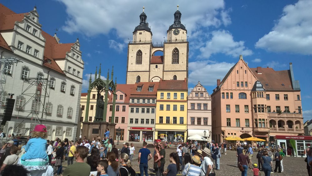 Luther's statue is on the left with his church in the center background with two spires as seen from city square as people gather for the start of the national celebration of the 500th anniversary of the Protestant Reformation.