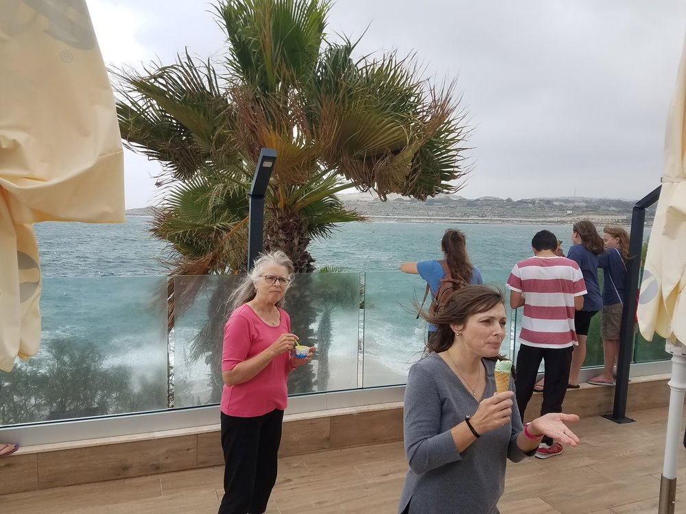 Nancy and Rachel trying to enjoy ice cream while being assaulted by a sudden Mediterranean storm kicking up some waves.