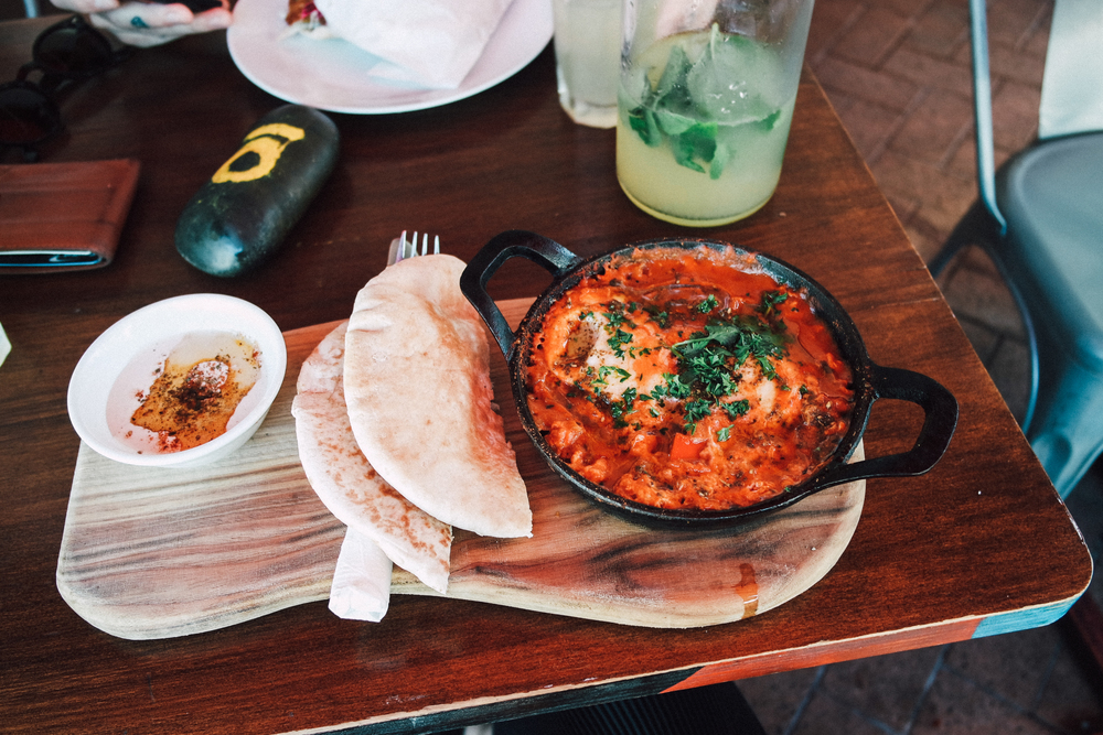 Shakshuka - poached eggs in tomato and capsicum sauce with tunisian spices w/ tahina and pita pocket