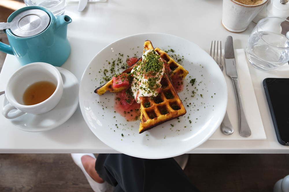 Turmeric & coconut waffle w/ rhubarb and lemongrass compote, greek yoghurt and ground pistachios @  The Modern Pantry