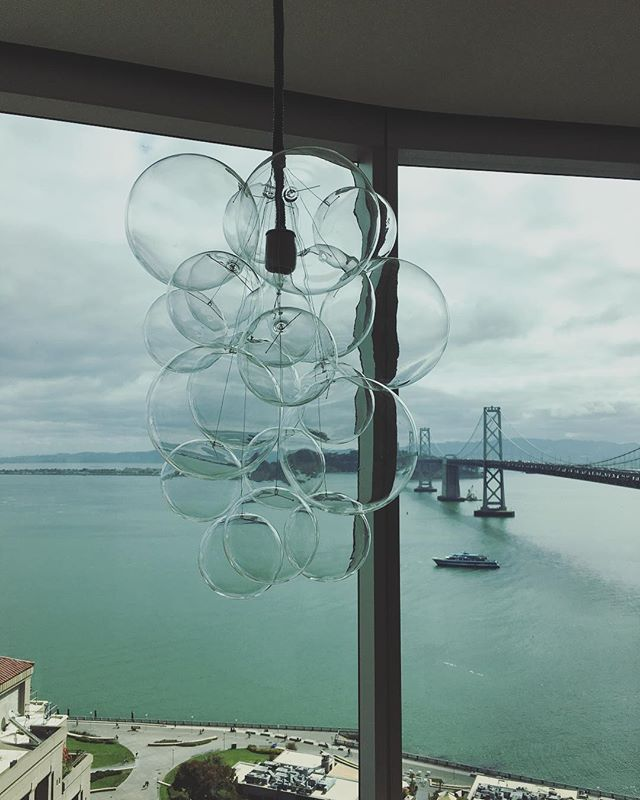 I believe honoring your environment is core to good design. So here, it was important that the DR table pendant would not obstruct the killer view but also it had to be a beautiful element in the design.  Mission accomplished I think. And I love that they kind of reference water bubbles!