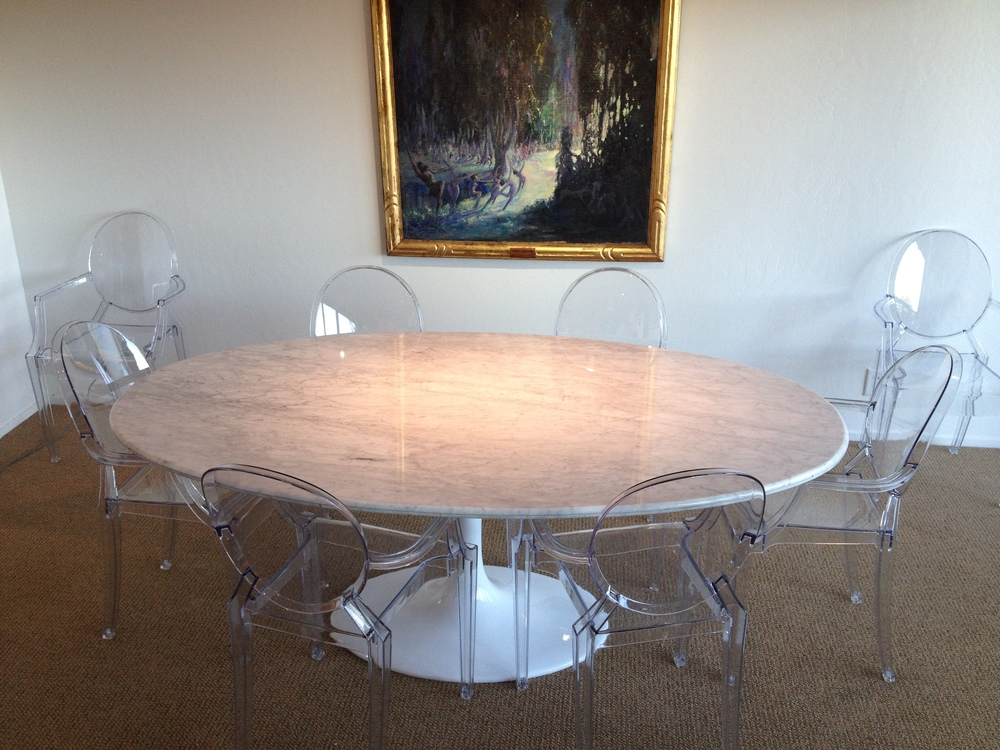 White Carrera Modern Marble Dining Table designed by Charles Eames floats with clear Ghost Chairs designed by Phillip Stark