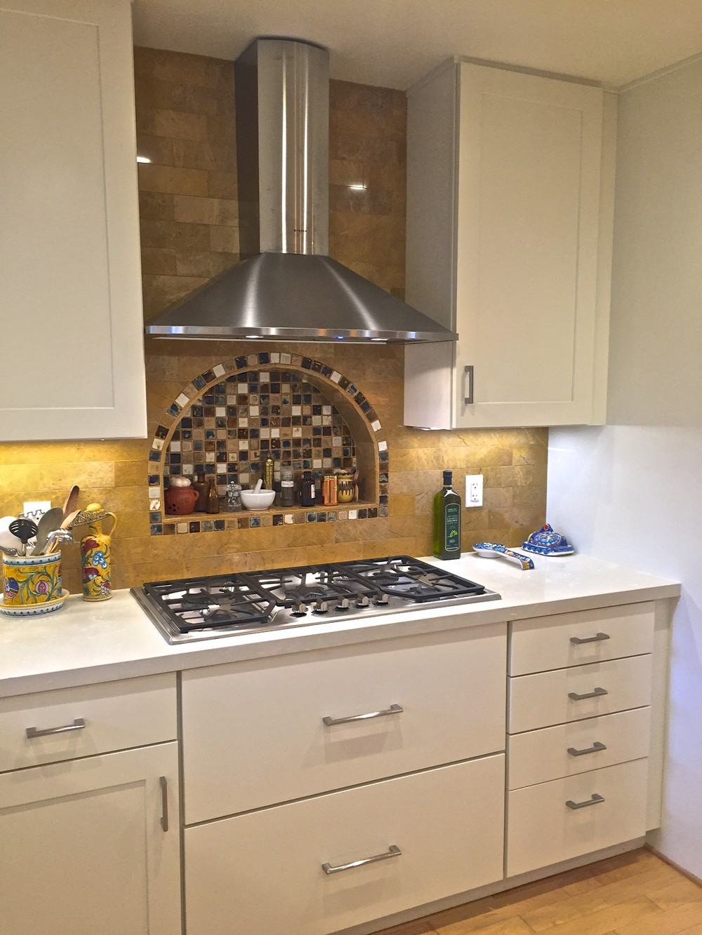 Recessed niche behind gas cook-top focuses the heart of the kitchen to the cooking area.