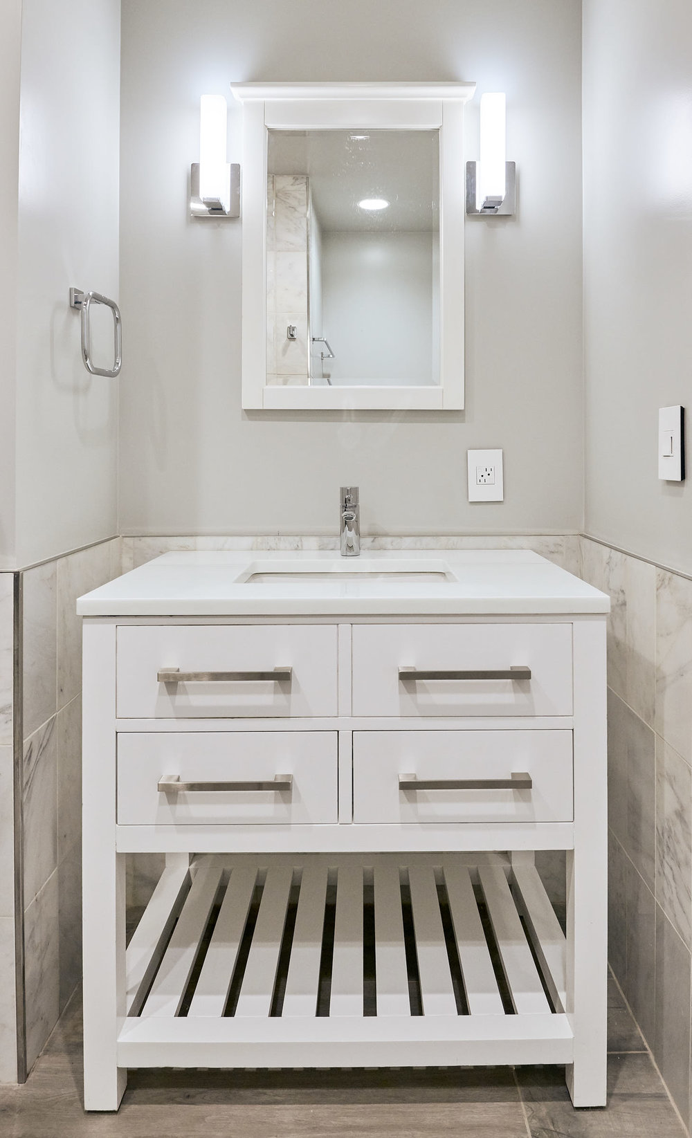 White Carrera Marble tiles, White Quartz Counter, White Cabinet all make for a classic bathroom.