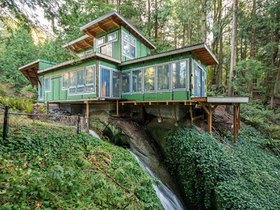 Delicately perched over a seasonal waterfall, this house has undergone a transformation from the ground up.