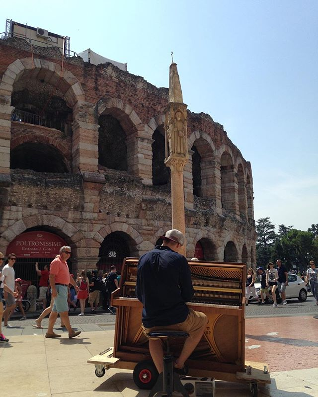 """Travel and explore. Visit and learn. Observe and absorb.  Find original views! A passerby plays a public instrument by the iconic Arena di Verona in a sunny summer day."" #Verona #Italy #walking #music #travel #summer #sonderon #dreamschest"