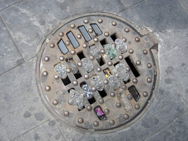 "Bottles inside Sewer Cap (Downtown, Mexico City), 2008. From the series ""Found Objects""."