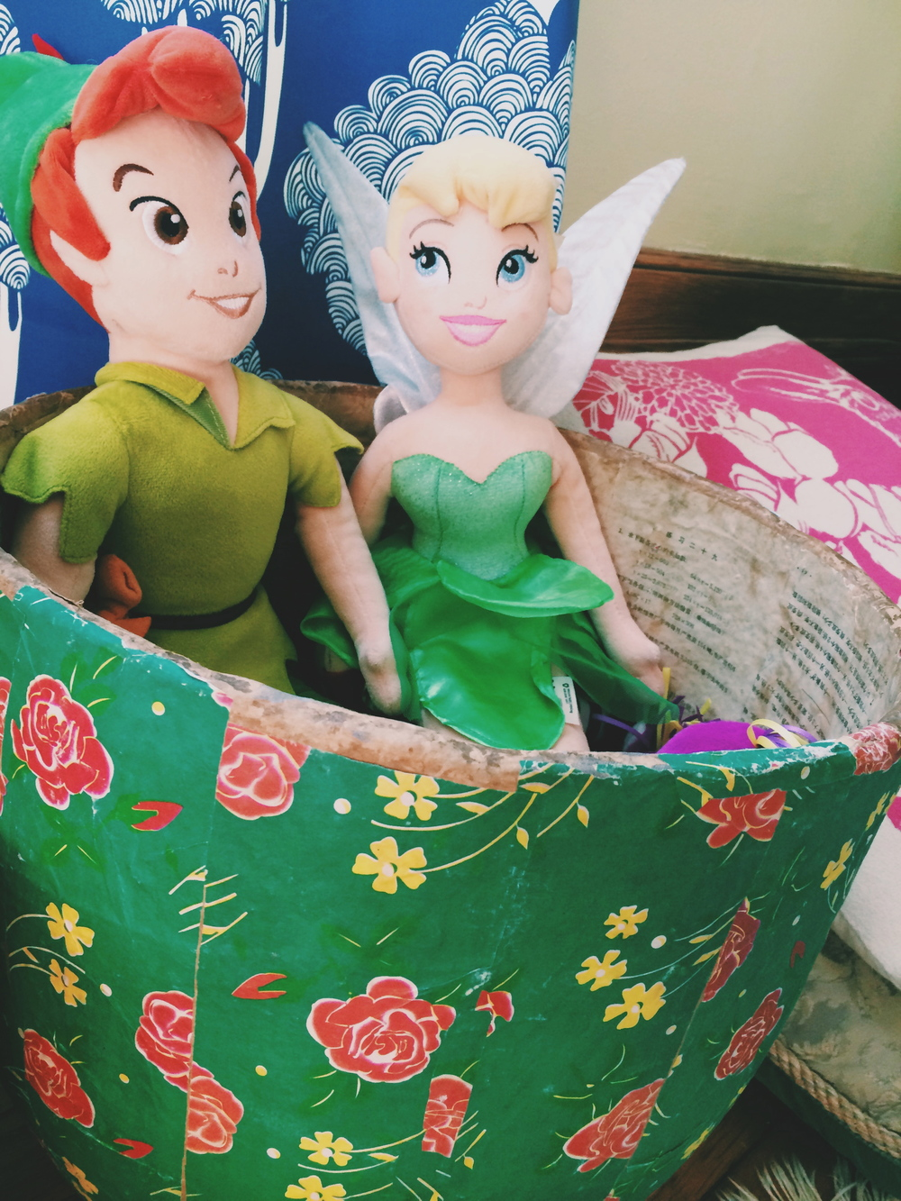 "Repeat after me...toy storage can be beautiful and functional! Vintage floral basket from Shabby Chic. Rabbit pillow from Erin Flett for my husband's mother ""Bunny"" who watches over us. Tinkerbell and Peter Pan because magic is very alive for both the kids and adults who live here."