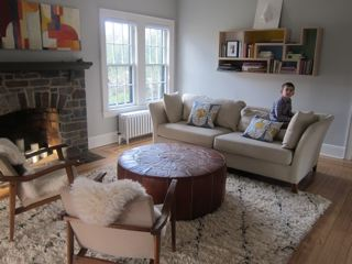"Using beloved existing seating, we transformed this family's living room by adding elements of textural beauty and pops of color. Cozy-chic Moroccan rug from Anthropologie and sheepskin throws from Ikea, Color-blocked ""Tetra Flat"" shelving from Brave Space Design adds color. functionality and fun."