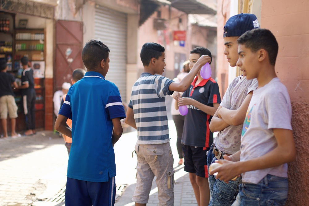 local boys playing with water balloons in the heat of the Medina