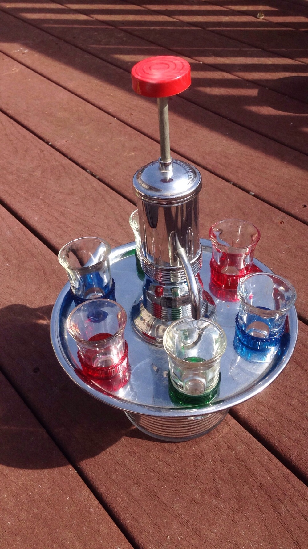 Glass decanter with pump, chrome revolving shot glass tray.