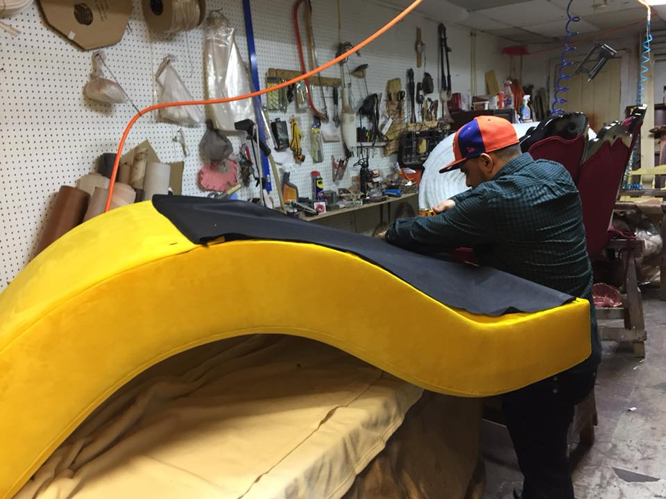 The Upholsterer works to add the dust cover, the final finishing touch!  You can see in the background he does some amazing pieces and I have seen him working on more than one Victorian piece.  They always look fabulous!