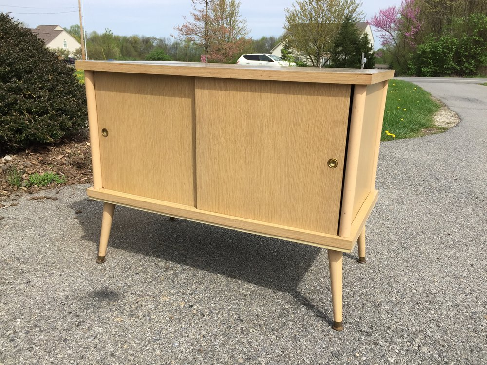 A great blond wood and Masonite cabinet. Use for records or storage in atomic style.  These do not stay around long.  Comes with a cute collapsible metal shelf.