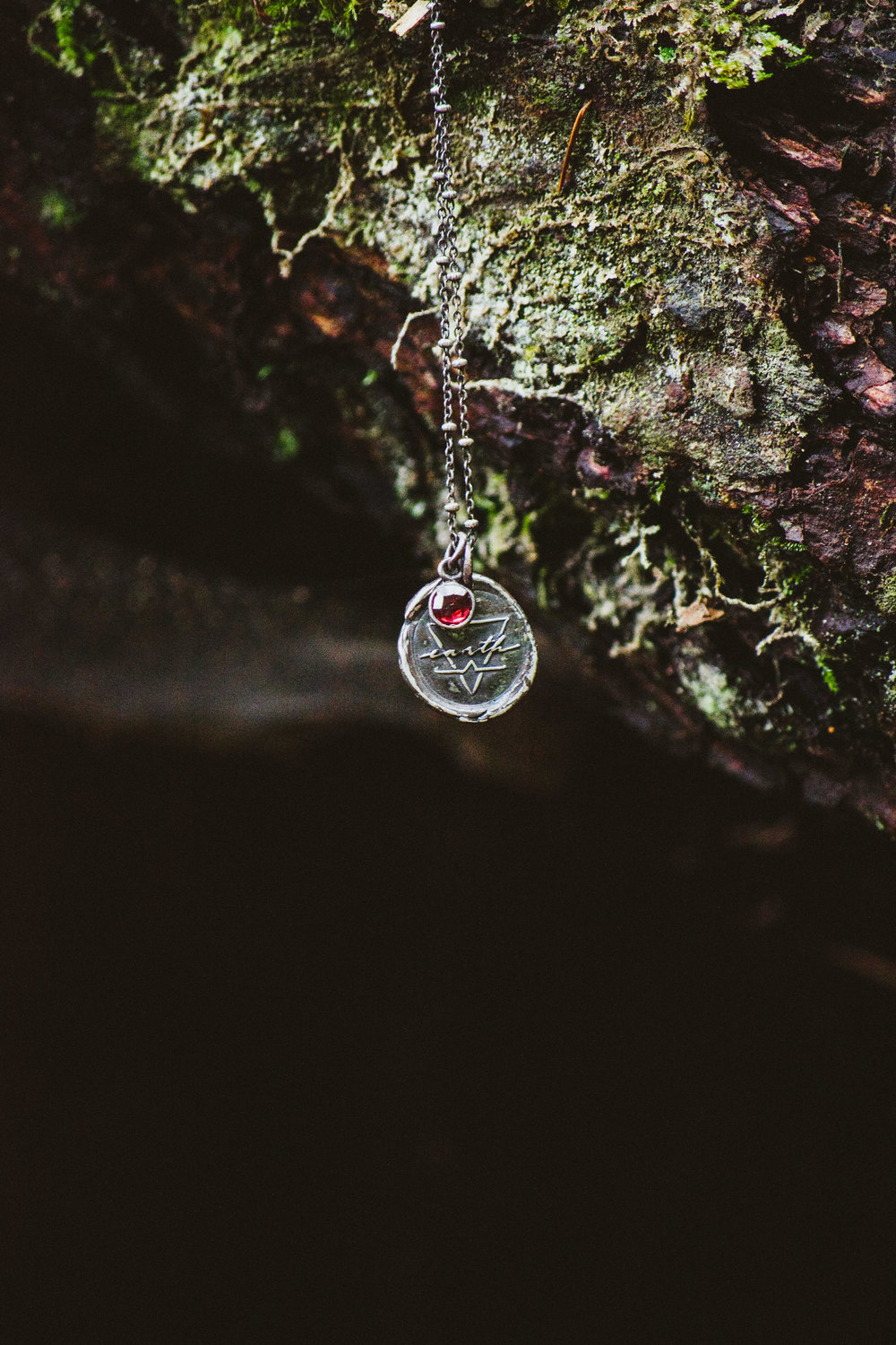 Earth - Earth is represented by red garnet.The earth element is feminine, deep, and strong. It is dark, rich soil, rocky boulders, and intricate root systems. It is the warm pulse deep within the core of mother earth; the heartbeat of Gaia.Earth grounds, nurtures, and sustains.