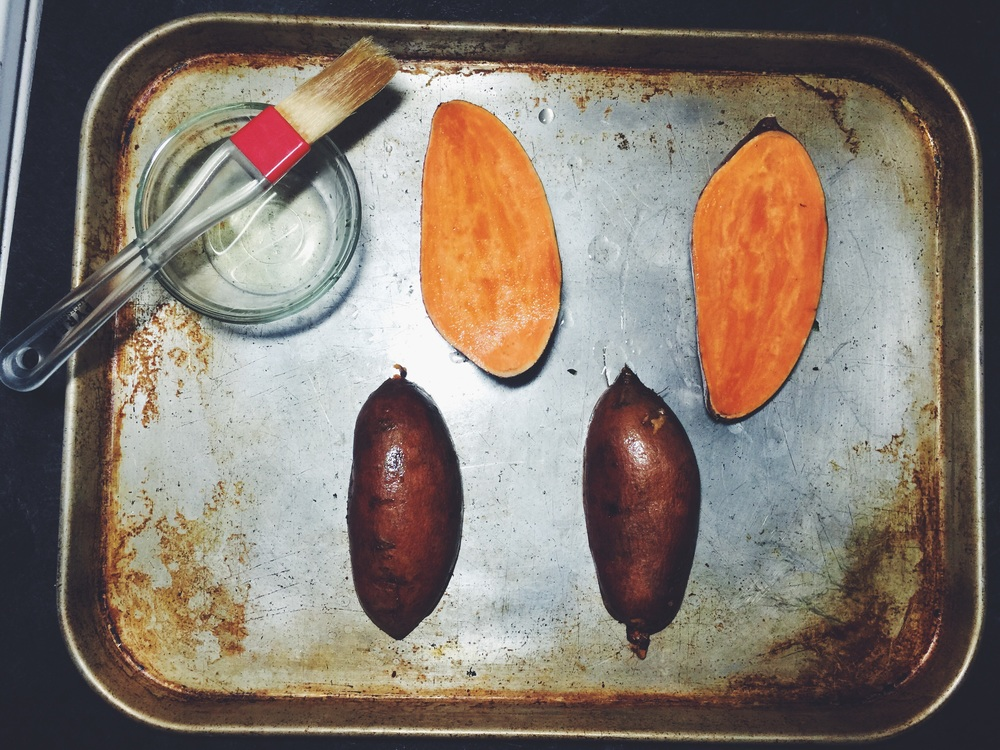 brushing olive oil on sweet potatoes