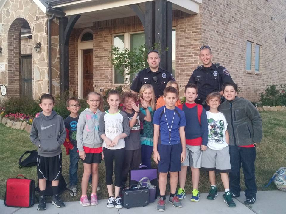 Officer Kyle Schwanz and Officer Doug Williams at the bus stop with Harvest kiddos