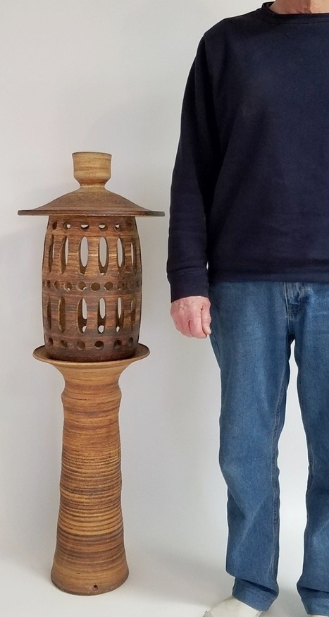 """023.  Garden lantern, 3 pieces 44"""" tall, 15"""" wide, - whole – all 3 pieces base – 23.25"""" tall, 11.25"""" wide center – 21"""" tall, 7.5"""" wide lid – 8"""" tall 15"""" wide. 3 pieces + wheel thrown, unglazed stoneware, red iron oxide wash over all, cut out design in center piece. Hole in center for electrical wire, chip on top lip of base, hole on foot for electrical wire, marked with signed tape."""