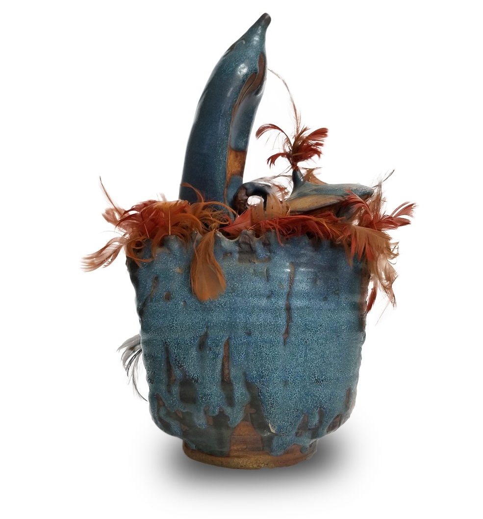 """- 021.17"""" tall, 9"""" wide, 7"""" deep, waxy blue glaze, wheel-thrown altered shape with added on wheel thrown shapes, textured sides and nest colored feathers, marked with signed tape, crack on bottom, top lg. add on piece broken off and glued on"""