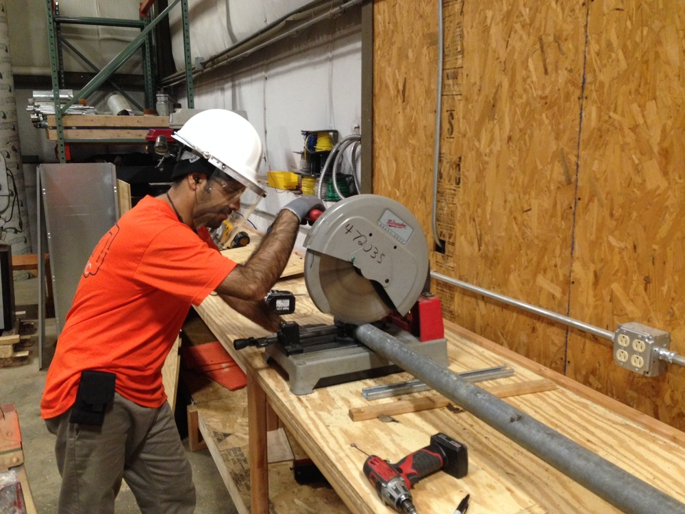 Mustafa Mohammad Asif cutting rigid conduit in preparation for threading.  Utilizing the metal cutting saw speeds up the threading process; in some cases multiple pieces of conduit can be cut at once, the saw cuts cleaner, which shortens the time, spent deburring before threading it.