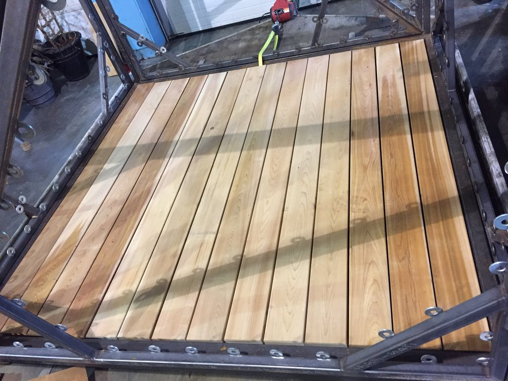 Like a glove!! The 2x6 cedar planks fit perfectly in the frame. Although this color scheme looks great, the floor boards will soon be stained black, and the frame will be white. Our goal is to have it look more approachable and less like the set of Mad Max.