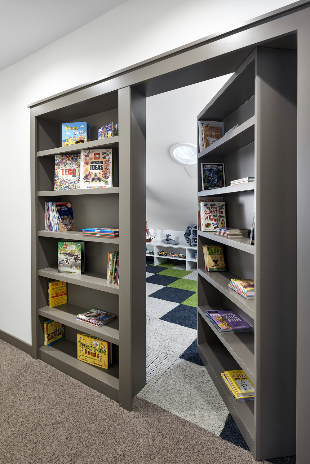Toy room hidden behind bookcases, designed by NewStudio Architecture