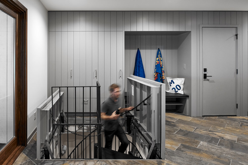Spiral staircase leads to sailing team changing area, designed by NewStudio Architecture