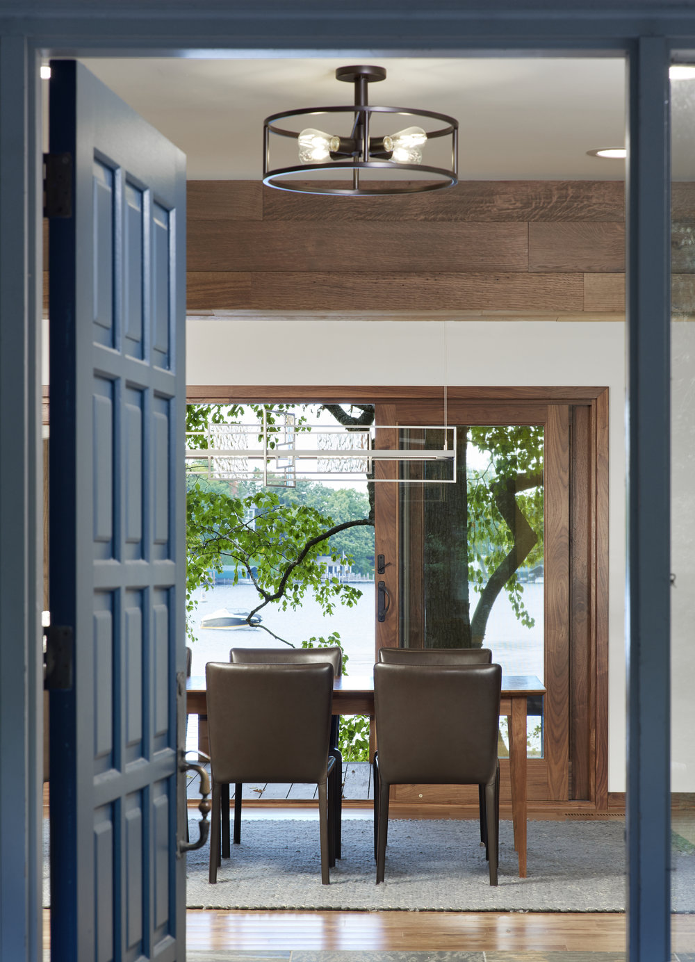 Blue interior door opens to dining room designed by designed by NewStudio Architecture with Lake Minnetonka view.