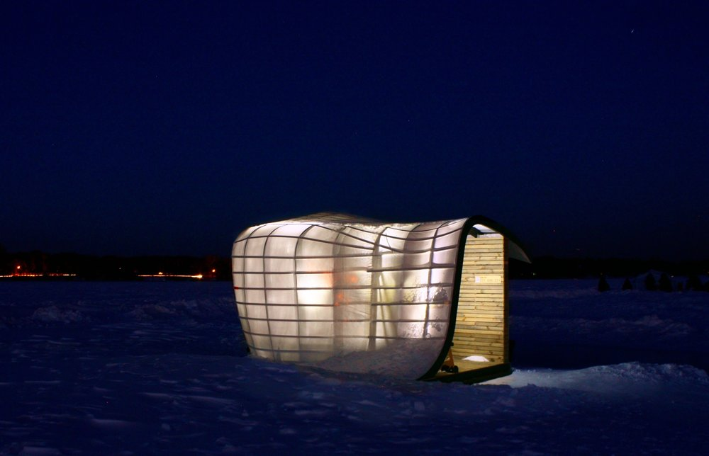 Nighttime exterior of lit-up art shanty designed by NewStudio Architecture