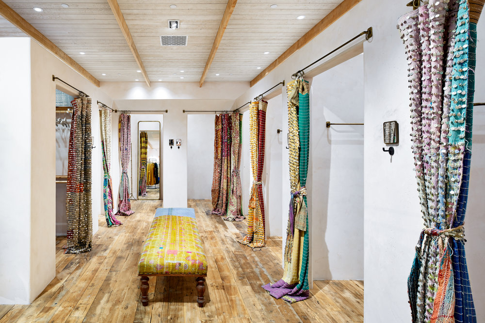 Rustic wood floor and bright curtains in fitting room area of Free People in Edina, Minnesota, created in collaboration with AOR NewStudio Architecture