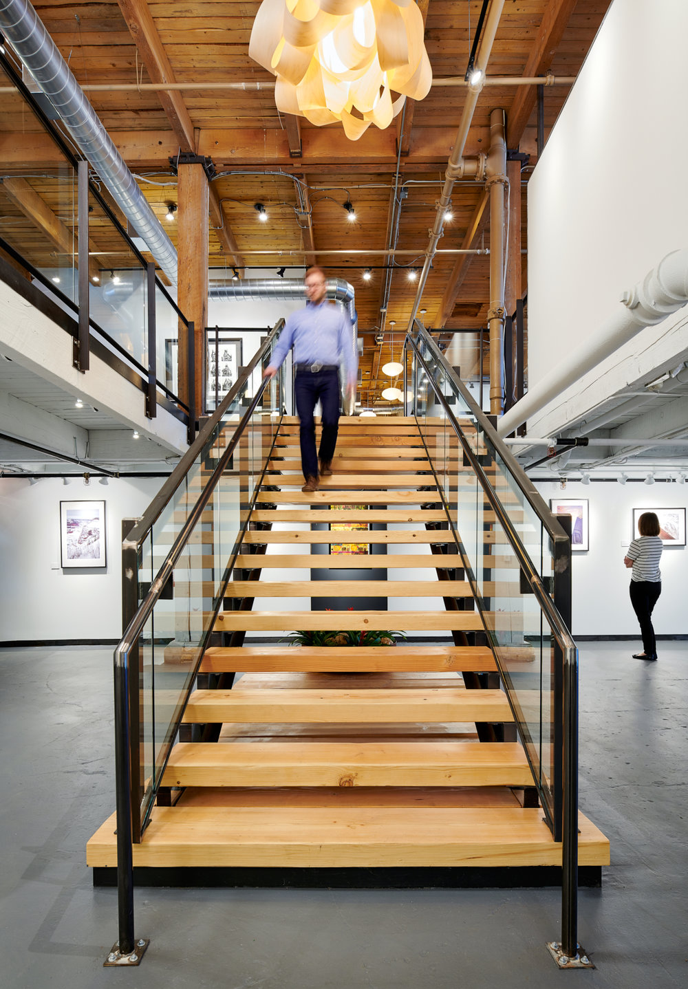 A custom steel and timber grand stair leads down to NewStudio Gallery at NewStudio Architecture's Saint Paul, Minnesota office.