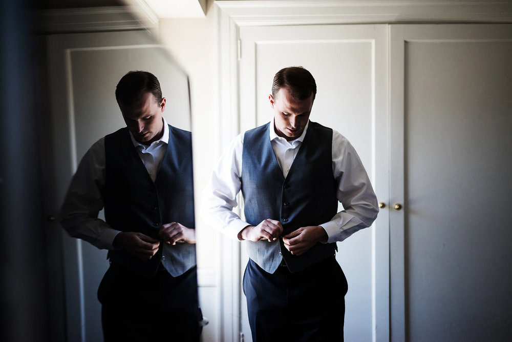 groom getting ready buttoning suit