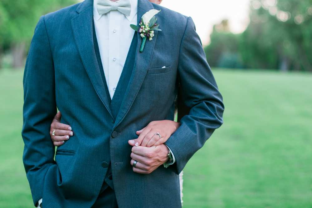 Groom suit details and boutonniere with bride's hand for New Prague Minnesota wedding golf course