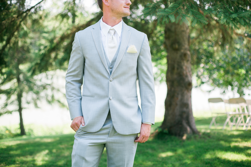 Groom's gray suit detail with pop of yellow and white tie at a summer wedding at Echo Valley in Wisconsin