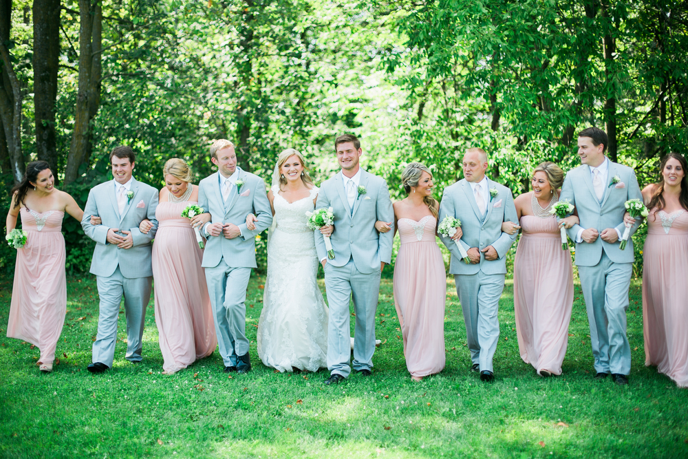 Candid lifestyle bridal party in summer wedding at Echo Valley in Wisconsin with blush bridesmaid dresses and gray suits