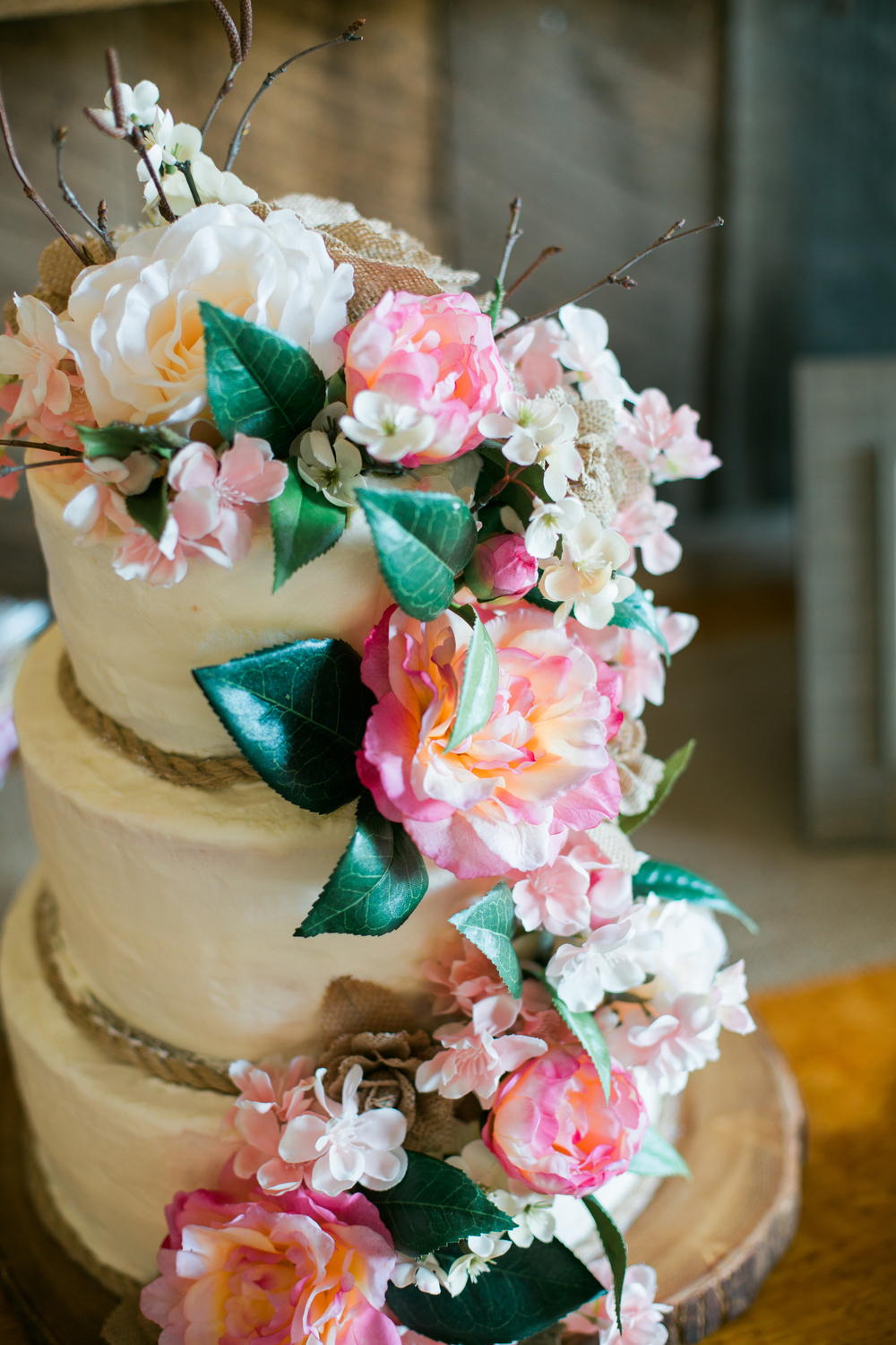 Wedding cake with rustic details and florals on top of wood slice for rustic wedding at Echo Valley